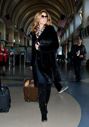 A glammed up Daisy Fuentes hit the airport in a black fur coat and leopard print scarf.
