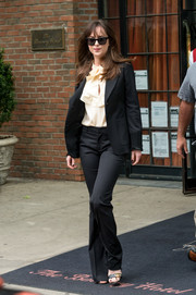 Dakota Johnson was spotted outside her New York City hotel looking smart in a black Gucci pantsuit.