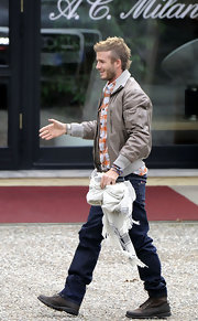 Beckham wears a rugged khaki jacket.