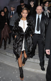 Cassie attended the high fashion event wearin a long black fur coat and a pair of black, lace up ankle boots with orange soles and a gold cap toe.