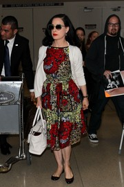 Dita Von Teese paired her print dress with a white cardigan.