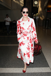 Dita Von Teese showed off a perfectly coordinated airport ensemble consisting of ruby-red ballet flats and a floral coat.