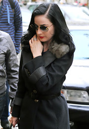"Dita is stunning in Paris with her flawless calf lenght jacket and rimless blue gradient lens ""Desmayo"" sunglesses with gold accents. The matching gold in her glasses and jacket make the look."