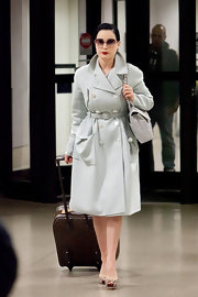 Dita Von Teese shows off her airport style in an egg shell wool trench coat.