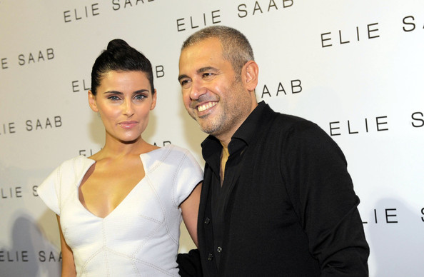 Nelly wears a classic bun and all white dress to this Elie Saab event.