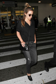Elizabeth Olsen kept it low-key in a plain black V-neck tee during a flight to LAX.