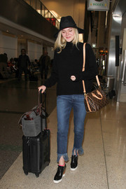 Elle Fanning teamed her sweater with funky fringed jeans.