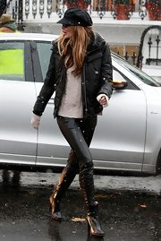 Elle MacPhereson braved the London snow in a pair of leather ankle boots. She paired the boots with matching pants and a fur lined parka.