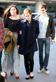 Emma wears a navy blue wool coat to LAX.