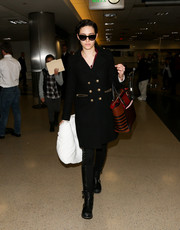 Emmy Rossum was looking edgy in Jimmy Choo moto boots, side-striped pants, and a wool coat as she made her way through LAX.