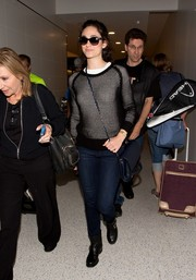 Emmy Rossum was spotted at LAX looking edgy-chic in a black mesh-overlay top and moto boots.