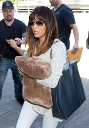 Eva Longoria was spotted at LAX carrying a black leather shopper bag along with a furry pillow.