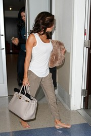 Eva Longoria completed her breezy airport look with silver thong sandals by Prada.