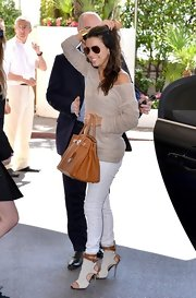 Eva Longoria arrived in Cannes wearing a pair of white and tan booties featuring sexy cutouts and ankle straps.