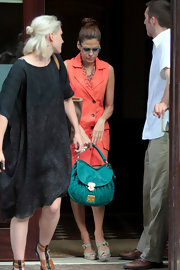 Eva Mendes accented her coral day dress with a bright turquoise leather Metalasse saddle bag.