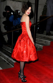 Elizabeth McGovern wore black strappy sandals with her red dress and sheer tights for a totally elegant finish.