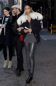 Chanel rocks a white fur collared coat with gray leather leggings during Fashion Week in New York.