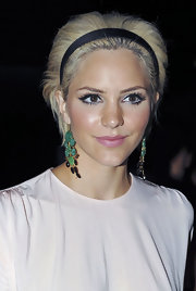 Looking chic for fashion week , she channels 1960's Edie Sedgwick with her blonde bob and statement green gemstone earrings.