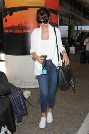 Felicity Jones completed her airport outfit with tight blue jeans.