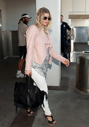 Fergie darkened her girly travel attire with a black Celine tote.