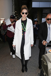 Gigi Hadid looked cool in a white A.L.C. coat layered over a Versace sweatshirt while making her way through LAX.