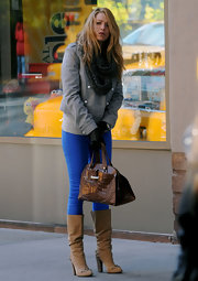 Black paired her bright blue skinny jeans with a pair of tan suede, knee high, studded boots.