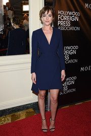 Dakota Johnson went for understated sophistication in a navy coat dress by Christian Dior during the HFPA Grants Banquet.