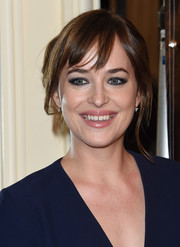 Dakota Johnson opted for a messy loose bun with wispy bangs when she attended the HFPA Grants Banquet.