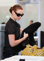 She is wearing dark brown framed sunglasses with a solid black lens.