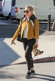 Hilary Duff gave her gym clothes an edgy punch with an ochre, black, and white suede jacket.
