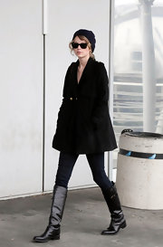 Taylor wears an A-line black coat with skinny pants and black boots for her arrival in Venice.