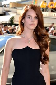Lana Del Rey wore her auburn hair down in cascading curls for her first appearance at the Cannes Film Festival.