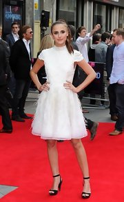 Lucy Watson kept her red carpet look classic and chic with a white embellished dress that featured a soft feathered skirt.