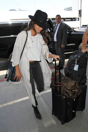 Nikki Reed took a flight out of LAX wearing a white duster over a crop-top.
