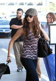 Nina Dobrev wore a taupe woolen newsboy cap while walking through LAX.