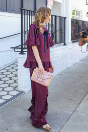 Jaime King stepped out of Au Fudge sporting this sweet pink envelope clutch and purple outfit combo.