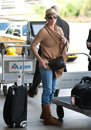 Jaime Pressly hit the airport in a pair of straight leg jeans, a jaunty fedora and a tan shawl collar cardigan.
