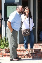 Julia Louis-Dreyfus teamed a tan leather shoulder bag with a white blouse and jeans for a scene of her new film.