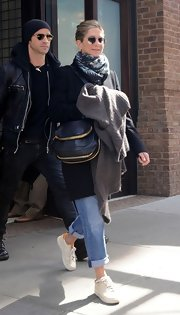 Jennifer Aniston paired her covered-up look with a black multi-zip purse.