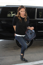 Jennifer Garner kept cozy in a black crewneck sweater for a flight out of LAX.
