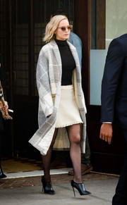 Jennifer Lawrence stepped out of her hotel looking retro in a white Oscar de la Renta tweed mini skirt paired with a black turtleneck.