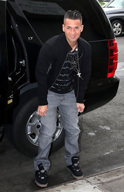 Mike wears a pair of black canvas sneakers with his jeans and track jacket while out LA.