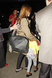 Angelina Jolie used a practical oversize leather messenger bag while traveling with her family.