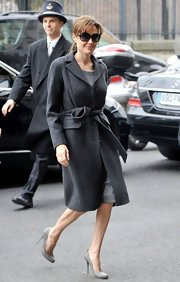 Angelina wears a charcoal wool coat with classic Jackie O sunglasses.