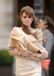 Angelina looks sweet and sophisticated with her loose half up hairstlye and bangs. This lighter color washes her out a bit but Angelina always looks gorgeous.