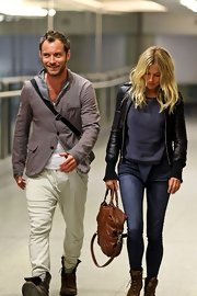 Sienna Miller isn't one for matchy-matchy. Headed back from Kenya with actor Jude Law, Sienna was spotted at the airport wearing a cool black bomber jacket with sweater knit cuffs. Bucking tradition, the Brit actress paired the black leather zip-up with a tan leather bag and boots. Who says your jacket has to match your shoes!