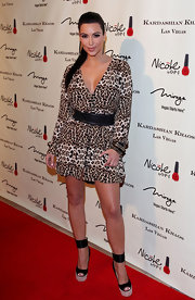 Kim Kardashian wore a wide black leather belt over her leopard print dress for the opening of Kardashian Khaos.