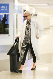 Underneath her coat, Karlie Kloss sported a long printed shirt by Celine.