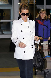 Kate dons a white trench with black buttons at the airport in Vancouver.