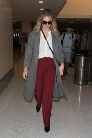 Kate Upton teamed red slacks with a white button-down shirt for her airport look.